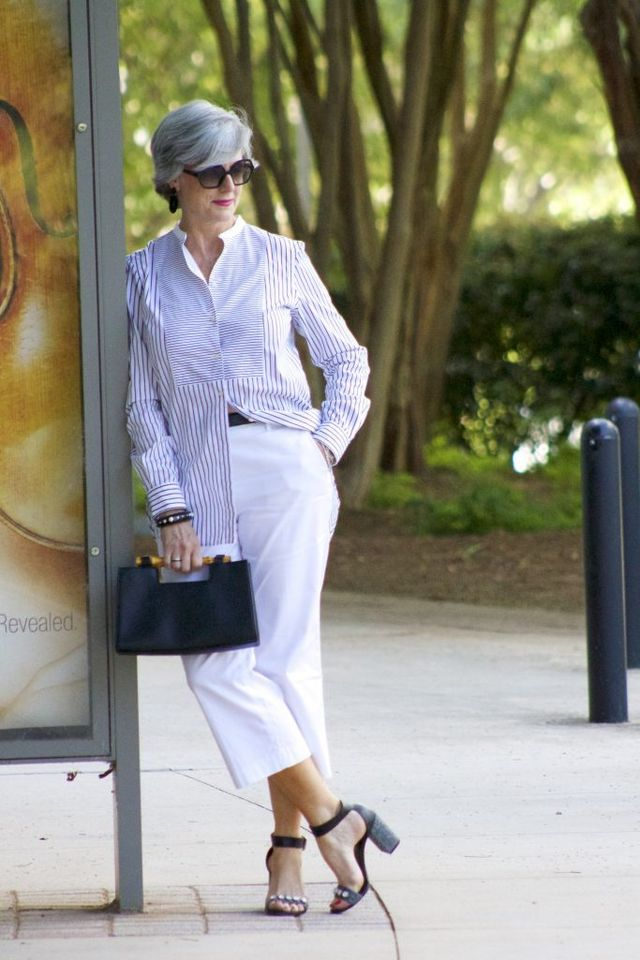 Summer casual outfit for 50 year old woman with white pants, long shirt and black sandals