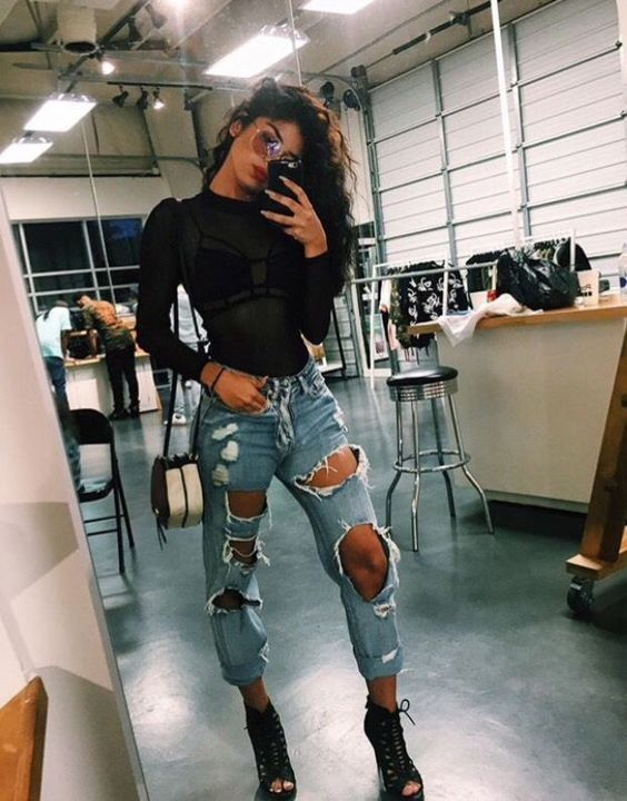 Club outfit with ripped jeans, black high heels and black transparent top