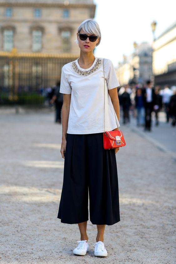 A white shirt with shiny accesories and culottes pants