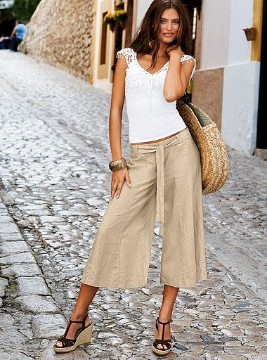 A white tank with lace accesories with beige culottes