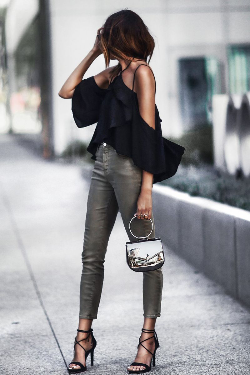 Grey jeans, an off-shoulder black top and strappy sandals for a summer going out outfit