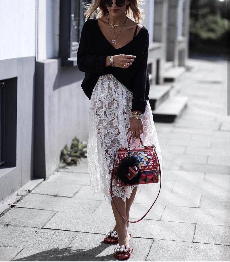 Casual summer club outfit wih lace midi skirt and a long-sleeve loose jumper with a deep V-neckline
