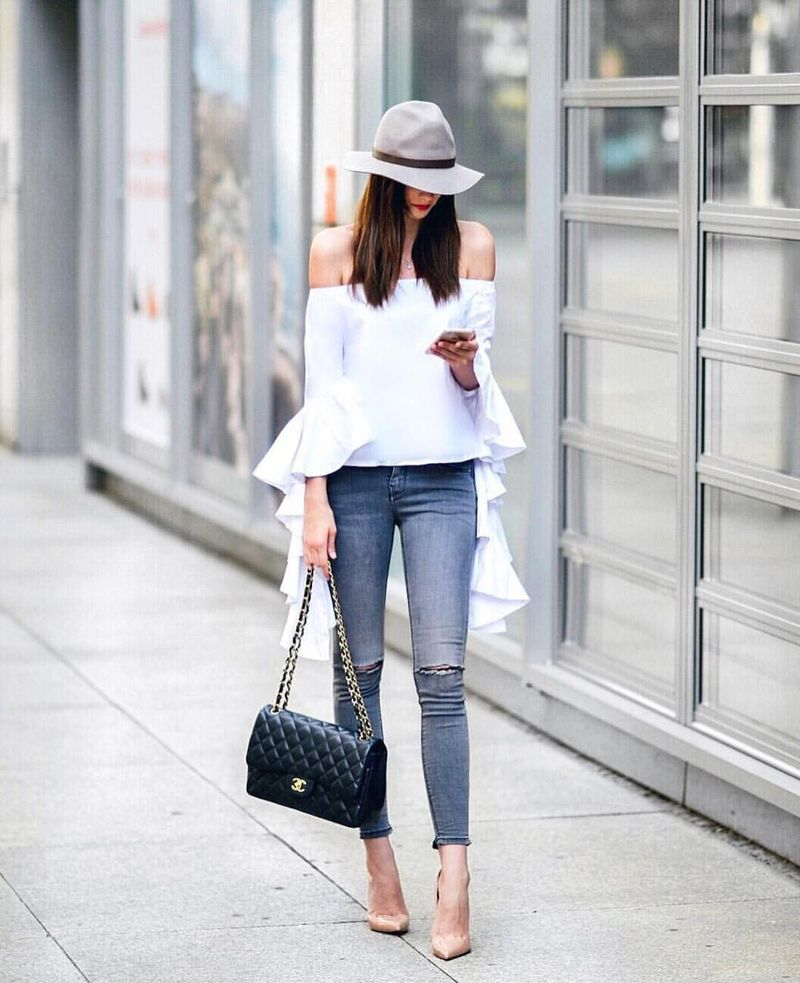 Club outfit with ripped skinny jeans, off-shoulder ruffle top and nude stilettos
